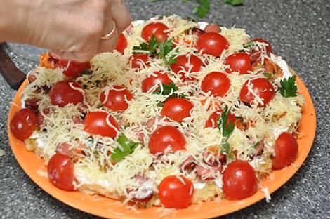 Сверху выкладываем половинки черри и еще немного посыпаем сыром и свежей зеленью. Накрываем сковороду крышкой и готовим пиццу, пока сыр полностью не расплавится.