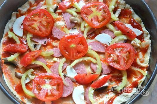 А затем выкладываем нарезанные помидоры. Отправляем противень с заготовкой в разогретую  до 200 градусов духовку на 20-25 минут.