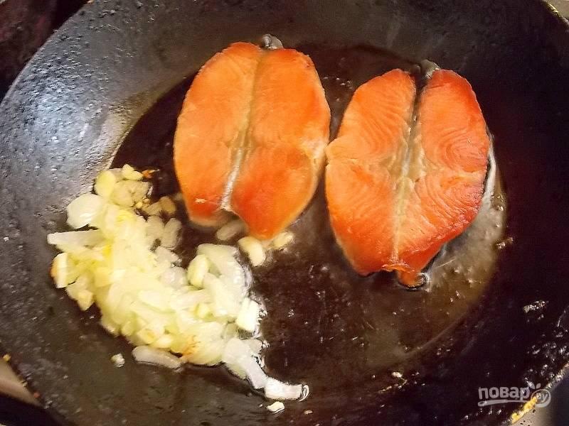 Отодвиньте лук и чеснок на край и положите рыбу. Обжаривайте в течение 5 минут.