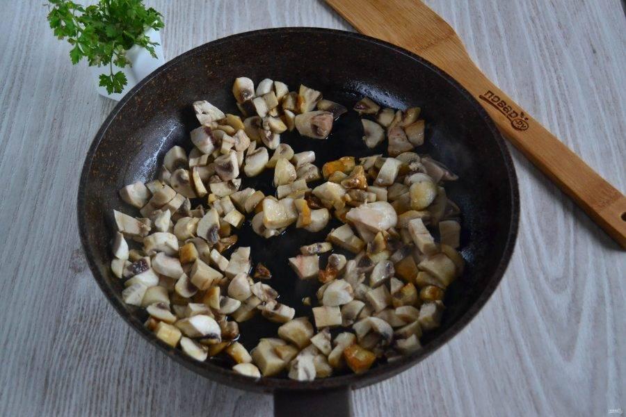 Шампиньоны очистите и нарежьте мелким кубиком. Обжарьте грибы на сковороде с растительным маслом.