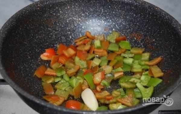 Болгарский сладкий перец почистите, удалив плодоножки, семена, внутренние перегородки, и нарежьте мелкими кубиками. На сковороде, в оливковом масле, обжарьте зубчик чеснока, добавьте нарезанный перец и немного соли.