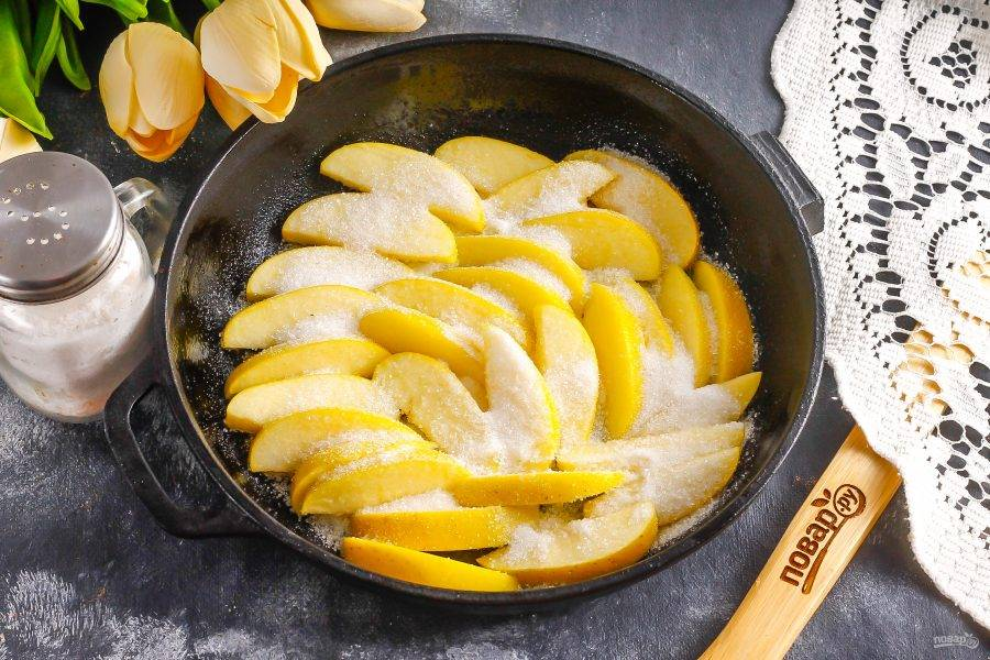 Яблоки промойте, очистите от семян и нарежьте ломтиками. Выложите на сахар и засыпьте оставшимся сахаром сверху. Разогрейте духовку до 200 градусов.