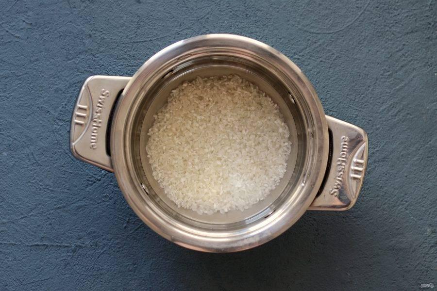 Рис промойте до прозрачности. Переложите в кастрюлю, налейте воды столько, чтобы она покрывала рис на 2 пальца. Доведите до кипения, убавьте огонь на минимальный и варите 15-20 минут.