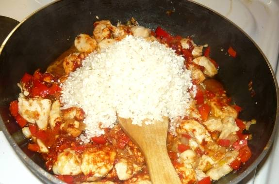 Добавляем рис, перемешиваем его с остальными ингредиентами и прогреваем буквально минуту на среднем огне.