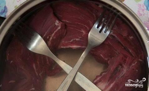 Мясо промойте и положите в кастрюлю. Залейте его раствором из холодной воды с солью. Оставьте в таком виде в холодильнике на двое суток, чтобы говядина не всплывала.