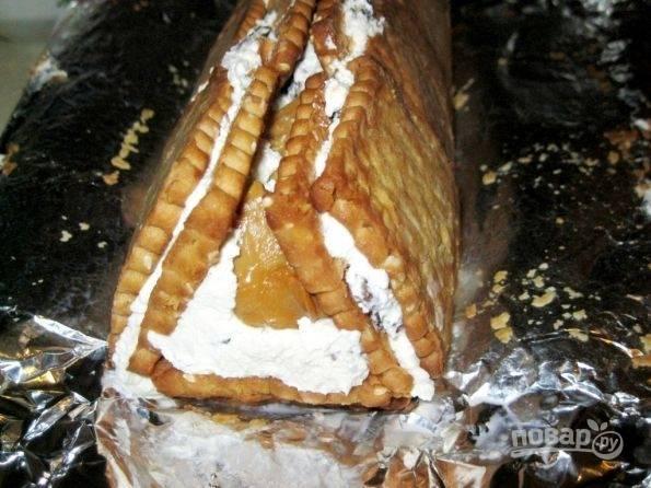 7.Возьмитесь за края пергамент и аккуратно сложите крайние стороны в форме треугольника, как бы формируя избу. Отправьте торт в холодильник в таком виде.
