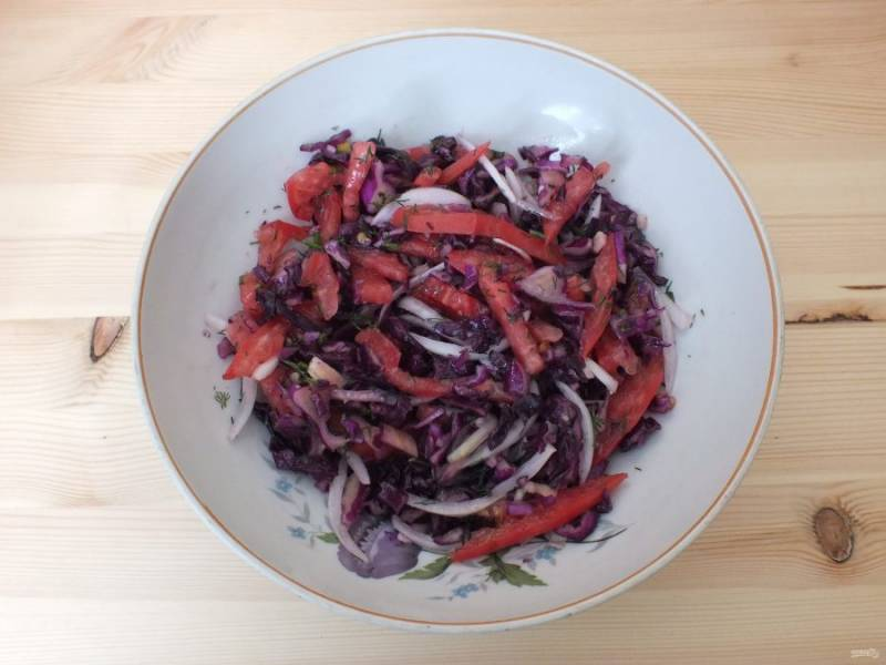 По истечении времени, к капусте добавьте помидор, лук, чеснок и укроп. Перемешайте, доведите солью и сахаром по своему вкусу. Заправьте 3 ст.л. растительного масла, еще раз перемешайте. Дайте настояться при комнатной температуре 15 минут.