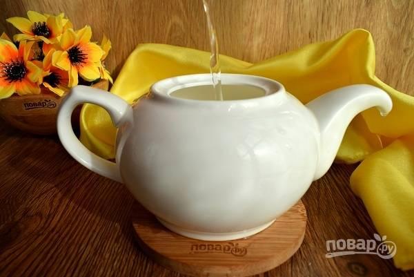 Фарфоровый чайник сполосните кипятком, засыпьте зеленый чай, залейте кипящей водой.