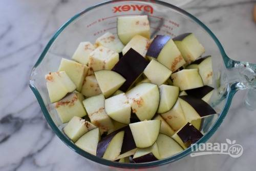 1. Вымойте, обсушите и нарежьте небольшими кубиками баклажаны. На сковороде с маслом обжарьте минутку чеснок, добавьте баклажаны. На среднем огне обжарьте минут 20, помешивая периодически.