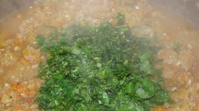 2. Овощную смесь на среднем огне доводим до кипения, и варим еще час, постоянно помешивая. затем добавим зелень и чеснок, варим еще 10 минут.