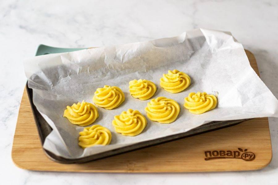 Отсадите печенье на пергамент с помощью кулинарного шприца. Выпекайте печенье в заранее разогретой до 180 градусов духовке 13-15 минут.