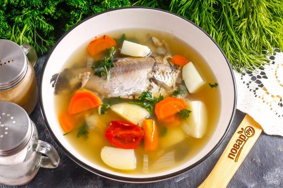Разлейте уху в глубокие тарелки, остудите при комнатной температуре, а после перенесите в холодильник на 1 час.