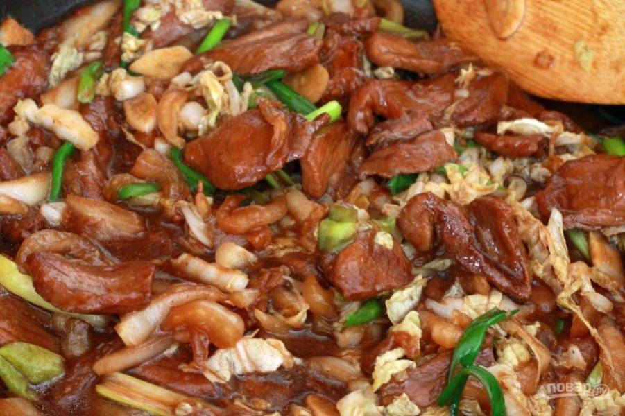 Спустя несколько минут в сковородку отправьте чеснок, белые части капусты и лука и прожарьте 1 минуту. Спустя установленное время отправьте зеленые части и готовьте еще 1 минуту.