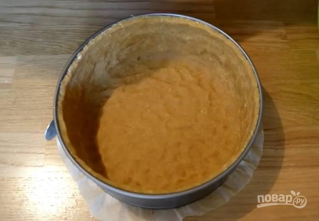 4. Застелите пергаментом дно разъемной формы, выложите туда печенье. Утрамбуйте плотно пальцами, сформируйте бортики.