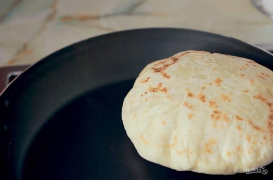 5. Тесто разделите на пять частей и раскатайте в лепешки толщиной примерно 0,7 мм. Далее на раскаленной сухой сковороде обжарьте питу с обеих сторон, периодически переворачивая, пока она не надуется.