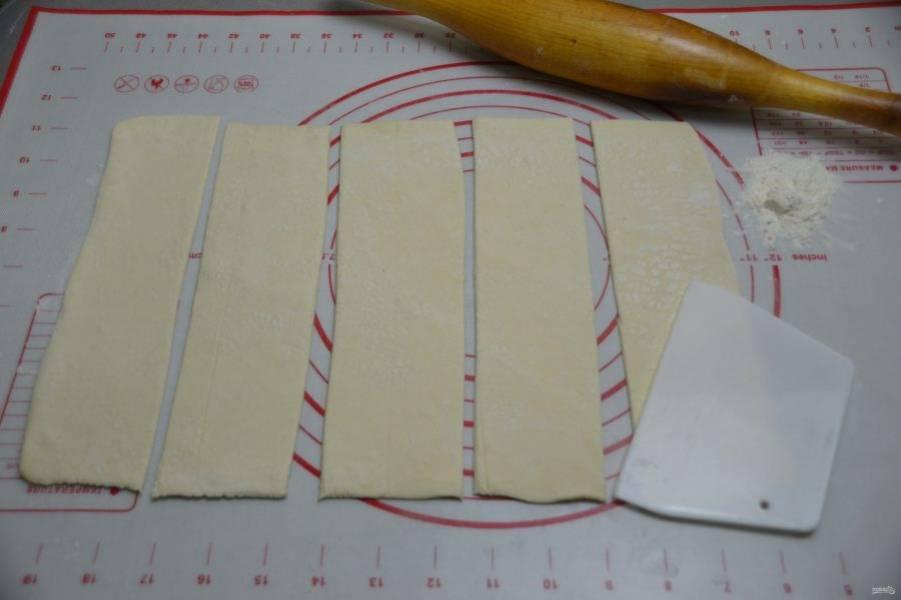 Слегка присыпьте рабочую поверхность стола мукой, раскатайте тесто в прямоугольный пласт и нарежьте на продольные полоски шириной примерно 7 сантиметров.