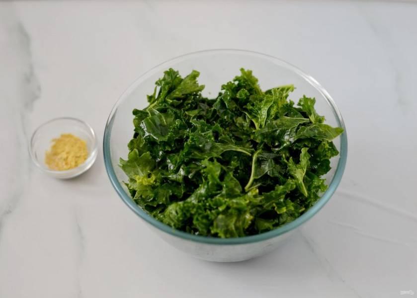 Переложите кейл в глубокую миску, полейте маслом и начните руками сжимать листья, чтобы они стали мягче.