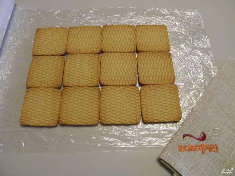 Расстелите пищевую пленку сложенную в два-три раза на столе. Выложите печенье в три ряда, длина рядов не важна. Если удвоить продукты, то тортик получится длиннее.
