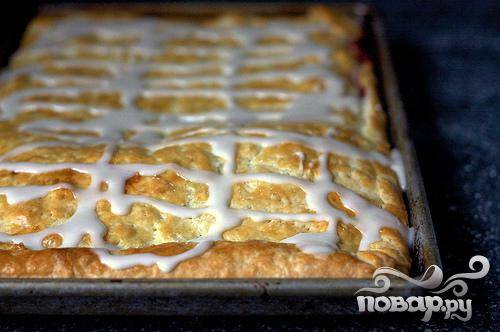 4. В миске перемешать сахарную пудру и молоко (или воду). Полить глазурью верхушку остывшего пирога. Нарезать пирог на кусочки и подавать теплым или комнатной температуры.