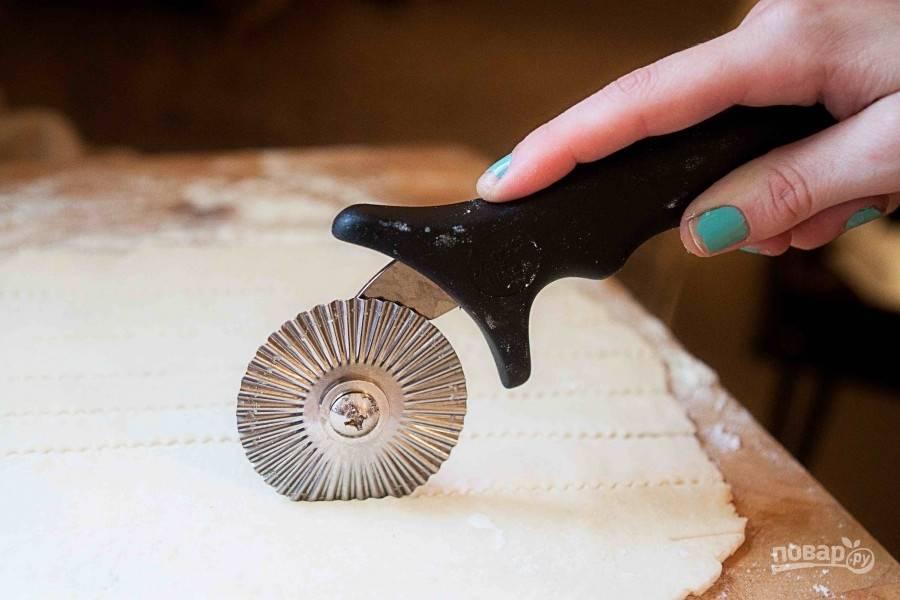 Включите духовку на 220 градусов. Оба пласта теста раскатайте на присыпанной мукой поверхности. Один выложите на дно и борта формы, слегка прижмите. Второй нарежьте обычными или фигурными полосками, как на фото.