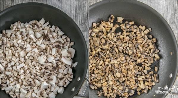 Хорошенько разогрейте сковороду с растительным маслом. Обжарьте на ней до мягкости мелко нарезанные шампиньоны. Затем переложите шампиньоны в салатник.