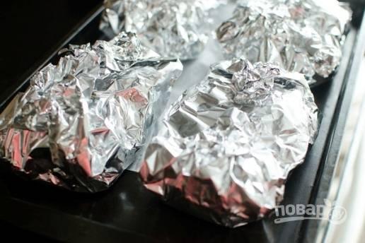 Плотно заворачиваем каждую порцию мяса с картошкой в фольгу, выкладываем их на противень. Отправляем в разогретую до 180 градусов духовку на 40-50 минут.