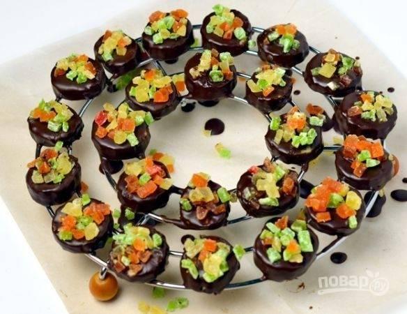 Все конфетки посыпьте цукатами. Оставьте их при комнатной температуре на пару минут, чтобы стёк лишний шоколад.