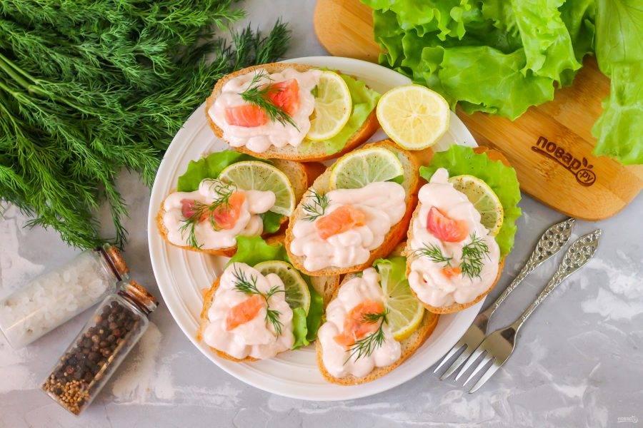 Приготовьте основу для подачи - на ломтики хлеба или багета выложите лимонную нарезку и салатные листья. Переместите мусс в кондитерский шприц и аккуратно выложите его на хлеб. Украсьте по вкусу и подайте к столу.
