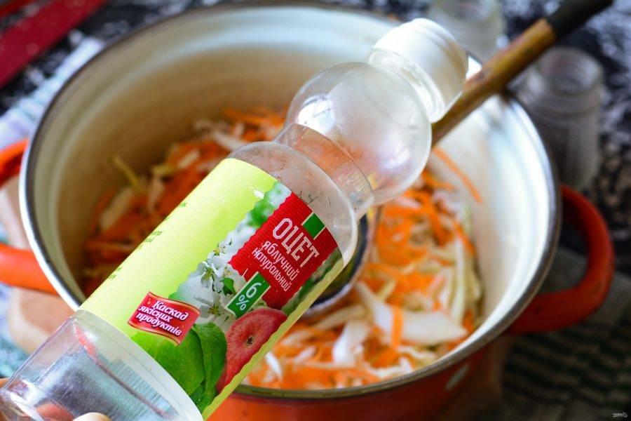 Влейте уксус и оставьте капусту мариноваться на 30-40 минут на столе. Слегка разомните руками, чтобы выделился сок.