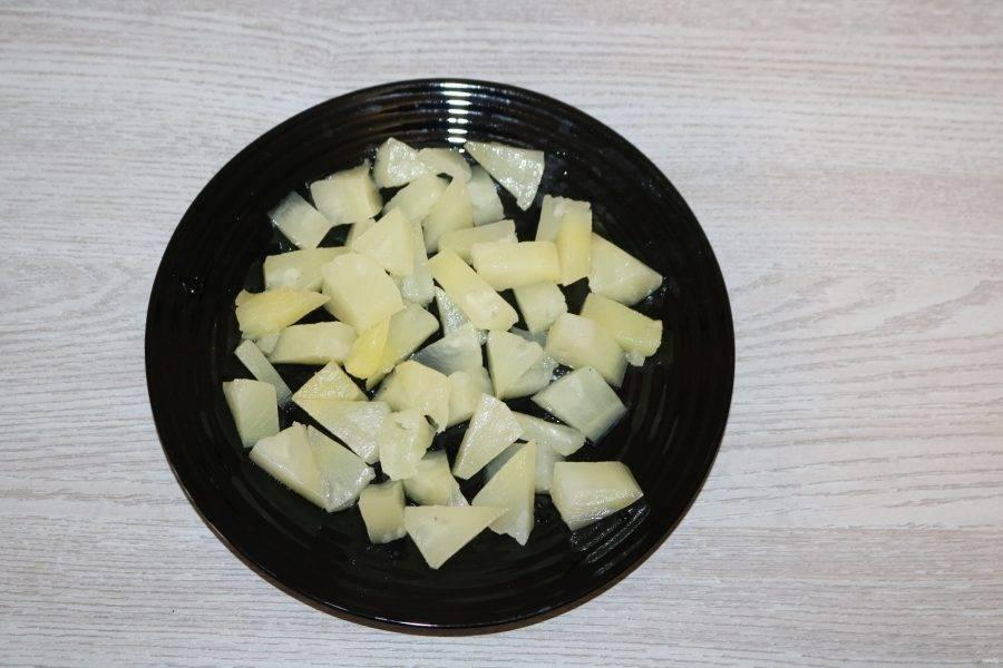 С ананаса слейте жидкость. Нарежьте кубиками, выложите на большую тарелку.