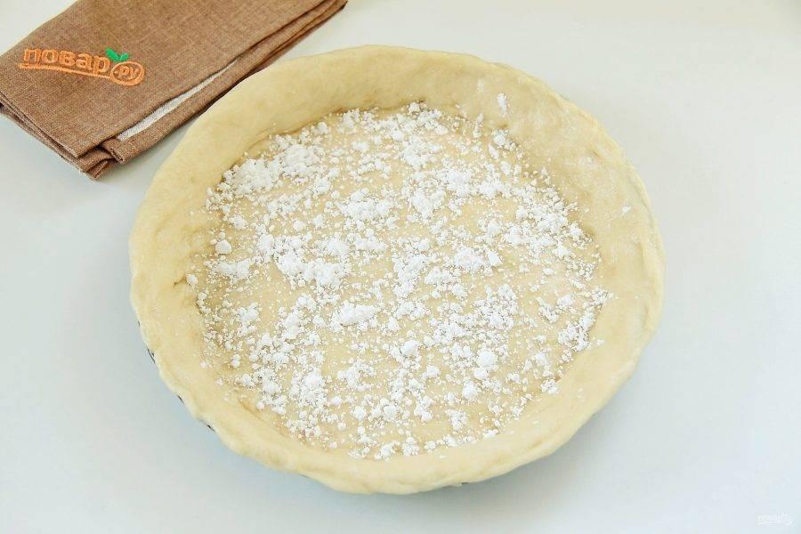 Разделите тесто на две части, одна - чуть больше. Большую часть теста перенесите в смазанную маслом форму для выпечки. Равномерно распределите и сформируйте небольшие бортики, высотой около 2 см. Дно присыпьте крахмалом.