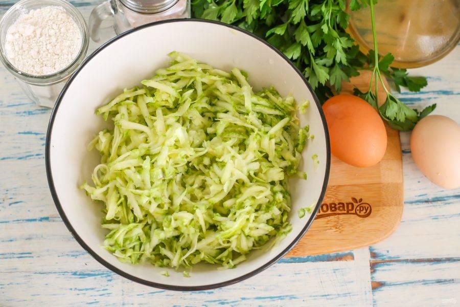 Кабачок промойте в воде, срежьте хвостики с обеих сторон овоща. Натрите плод на терке в глубокую емкость, всыпьте две щепотки соли и перемешайте. Оставьте на 5-6 минут, а затем отожмите массу от жидкости, иначе тесто не получится нужной консистенции.