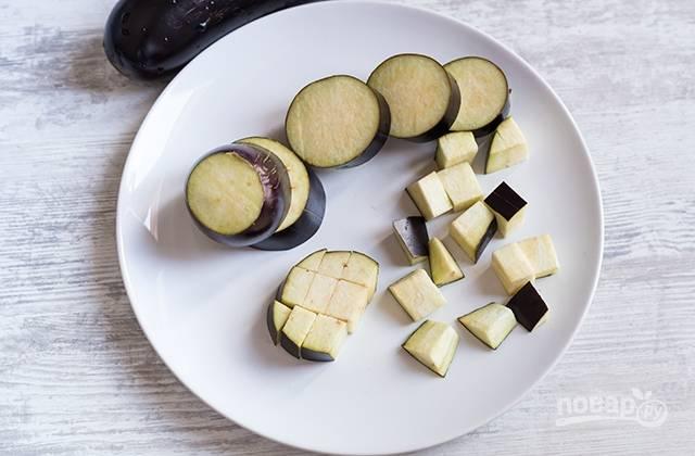 1.Вымойте баклажаны, отрежьте концы, нарежьте круглыми ломтиками толщиной около 2 см, затем – на кубики.