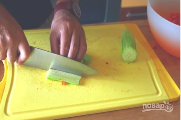 Очистите огурец от кожицы и нарежьте кубиками.