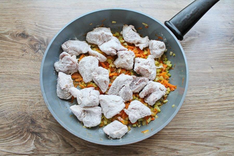Хорошенько обваляйте свинину в муке со всех сторон. Выложите ее в сковороду с оставшимися обжаренными овощами.