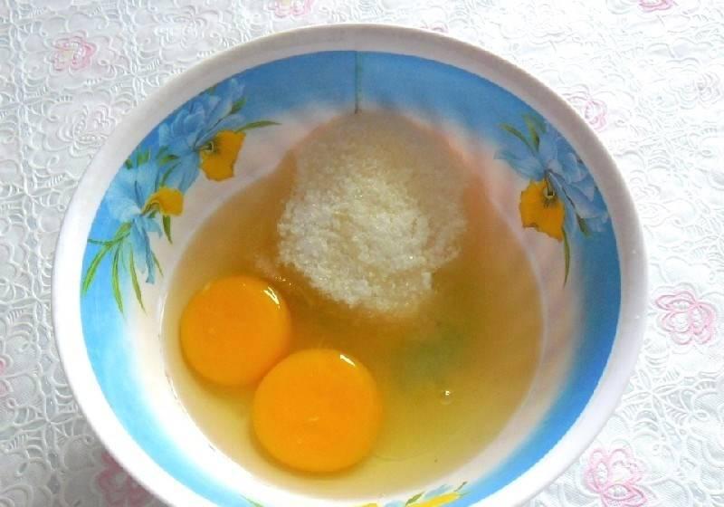В небольшую миску или пиалку вбейте сырые куриные яйца, добавьте соль и сахар. Затем при помощи венчика или миксера взбейте все до однородной массы.