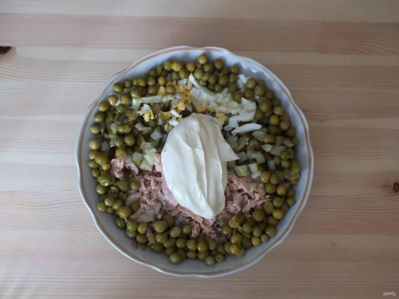 Нарежьте средним кубиком огурец, яйца, разберите на волокна рыбу. Отправьте все в салатник, добавьте горошек и майонез.