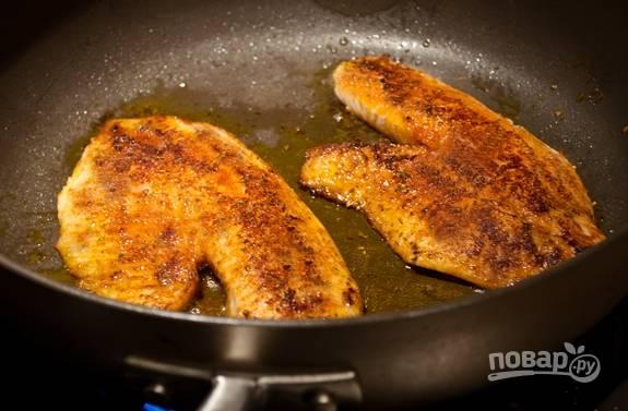 3. Разогрейте в сковороде масло. Обжарьте в нём тилапию до золотистой корочки с обеих сторон.