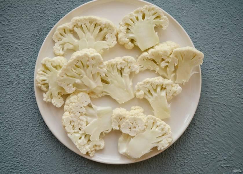 Разделите цветную капусту на соцветия, нарежьте их на плоские стейки.