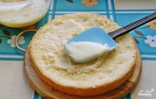 Пропитываем коржи сиропом. Смажьте один корж кремом, сверху накройте вторым коржом. Верх и бока торта также смажьте кремом.