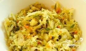 Для начала разморозьте тесто при комнатной температуре. Приготовьте начинку. Нашинкуйте капусту, натрите морковь на крупной тёрке. Лук измельчите, притомите его на масле до прозрачности. Затем добавьте к другим овощам, тушите их в течение 20 минут. Не забудьте поперчить и посолить, а также кинуть измельчённый укроп.