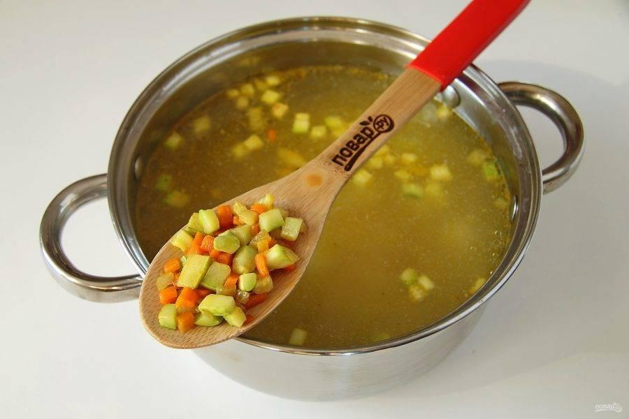 Добавьте обжаренные овощи. Доведите содержимое кастрюли до закипания и варите суп еще примерно 5-7 минут, до готовности всех ингредиентов.