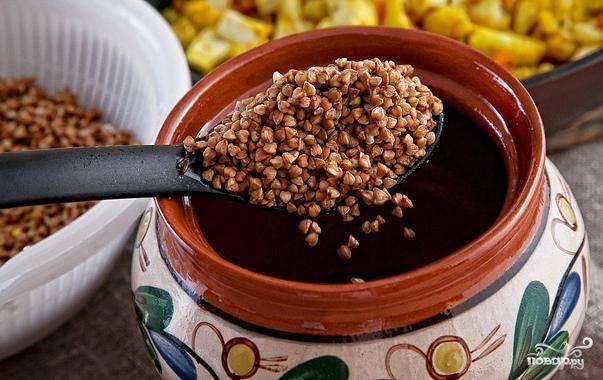 Гречку хорошенько промываем под проточной водой. Затем горшочки смазываем сливочным маслом. Выкладываем в глиняную посуду слой промытой гречки.