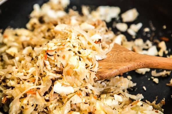 10. Отварные яйца нужно остудить, нарезать мелкими кубиками и добавить к капусте. При желании начинку можно поперчить немного.