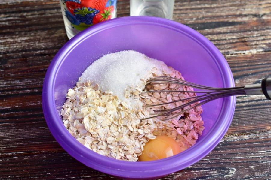 В миске соедините яйцо, хлопья и сахар. Все перемешайте венчиком.