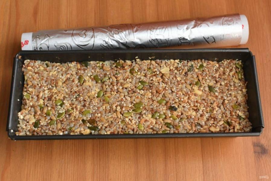 Выложите массу в подготовленную форму и утрамбуйте. Этот хлеб не поднимается, поэтому можно наполнять форму до краев. Накройте форму фольгой.