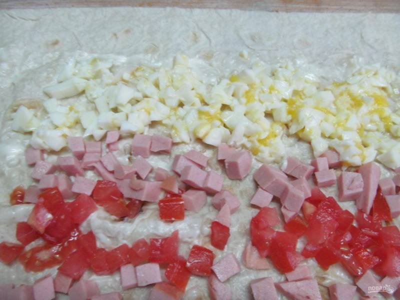 Вареные яйца нарезаем мелким кубиком и выкладываем последней полоской на край лаваша.