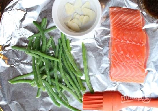 1. Для начала нарежьте тонкими слайсами чеснок. Также сделайте соус, смешав соевый соус с мёдом. Филе натрите солью и перцем, полейте соком.