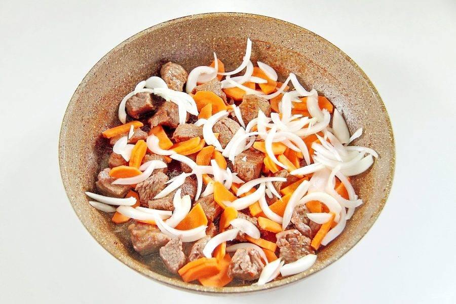 3. Обжарьте мясо со всех сторон до появления легкой румяной корочки, добавьте немного воды и тушите, накрыв сковороду крышкой на небольшом огне 40 минут. Затем добавьте нарезанный полукольцами лук и крупно нарезанную морковь.