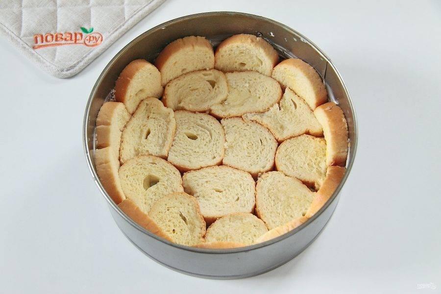 4. Сложите шарлотку слоями. В смазанную сливочным маслом форму уложите часть хлеба, закрывая дно и бока.